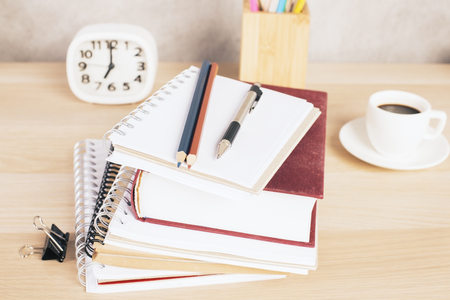 Closeup of books, coffee cup, clock and stationery items on wooden desktop. Education concept Imagens