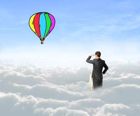 air baloon: businessman on cloud looking on air baloon Stock Photo