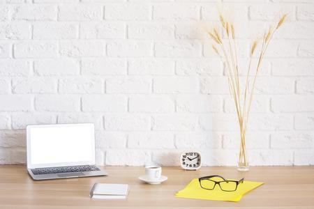 Lieu de travail lumineux avec ordinateur portable blanc vierge, bloc-notes, tasse à café, horloge, lunettes sur feuille de papier jaune et épis de blé sur fond de mur de briques. Maquette