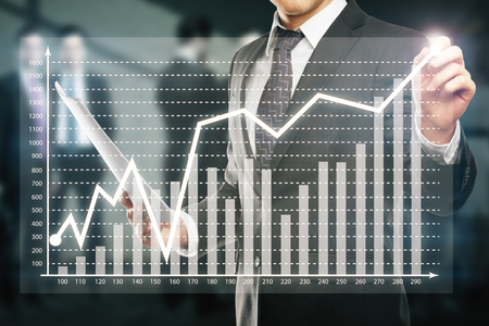 Businessman drawing abstract business chart on blurry background with other businesspeople Stock Photo