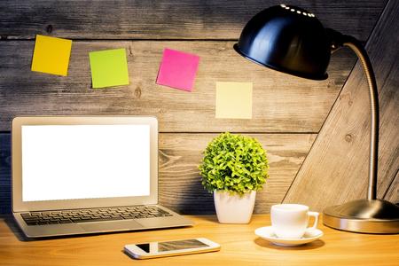 Kreativer Designerdesktop mit leerem weißem Laptopschirm, beleuchteter Lampe, bunten Aufklebern, Anlage, intelligentem Telefon und Kaffeetasse Spott oben. Attrappe, Lehrmodell, Simulation