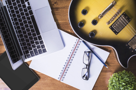 Top view of wooden desktop with blank tablet, spiral notepad, glasses, laptop, electric guitar, decorative plant and pencil