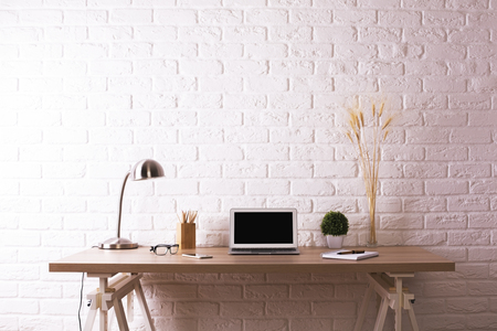 Front view of creative wooden designer workplace with blank laptop, decorative plants, table lamp, glasses and stationery items on white brick wall background. Mock up