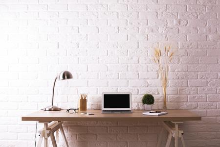 Vorderansicht des kreativen hölzernen Designerarbeitsplatzes mit leerem Laptop, dekorativen Pflanzen, Tischlampe, Gläsern und Briefpapiereinzelteilen auf weißem Backsteinmauerhintergrund Spott oben. Attrappe, Lehrmodell, Simulation