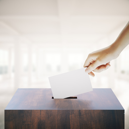 Hand with blank ballet casting vote into wooden ballot box on bright interior background. Voting concept. Mock up, 3D Rendering