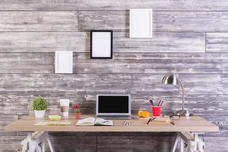 Modern designer desktop with blank laptop, picture frames above, plants, stationery and other items. Mock up Banque d'images