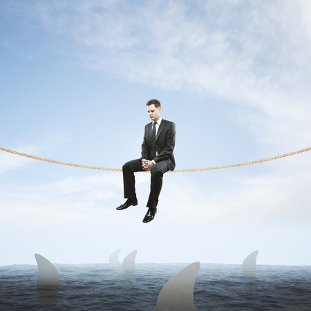 Risk concept with thoughtful businessman sitting on rope above sea full of sharks on sky background