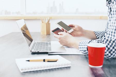 concepto de compras en línea con el hombre usando el teléfono inteligente y que sostiene la tarjeta de crédito en el escritorio de oficina con ordenador portátil, artículos de papelería y taza de café. Bosquejo