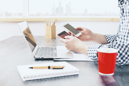 Online shopping concept with man using smart phone and holding credit card at office desktop with laptop, stationery items and coffee cup. Mock up