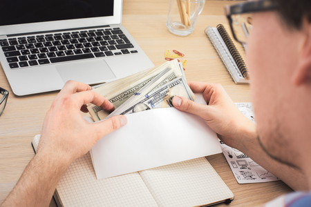 bribery: Businessman counting money above wooden office desktop with various items. Bribery and corruption concept Stock Photo