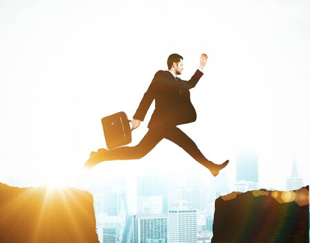 cliff jumping: businessman jumping on cliff, success concept