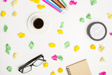 Messy office table with colorful crumpled paper pieces, coffee cup, pencils, eyeglass, notepad and clock. Top view, Closeup