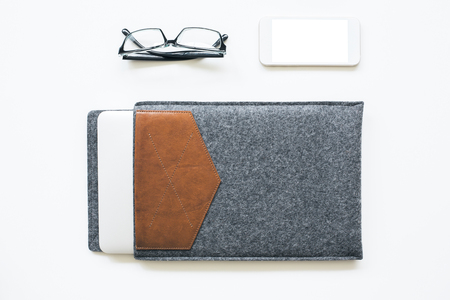 Top view of light table with blank white smartphone, glasses and closed laptop in grey and brown case. Mock up Banque d'images