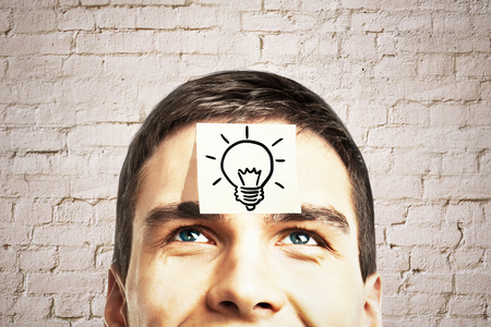 Idea concept with lightbulb sketch drawn on sticker glued to happy guy's forehead on brick background