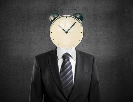 Concepto de gestión del tiempo con reloj despertador encabezado empresario sobre fondo de hormigón Foto de archivo