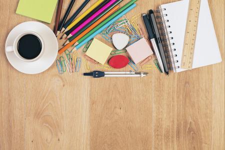 Vista dall'alto del desktop in legno disordinato con tazza di caffè e articoli di cancelleria colorati. Modello