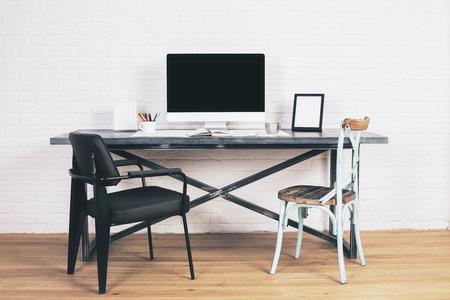 Sedia nera moderna e sedia blu creativa alla scrivania di design con schermo del computer vuoto e cornici. Modello