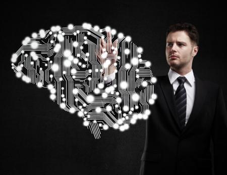 businessman presses circuit board in form of human brain