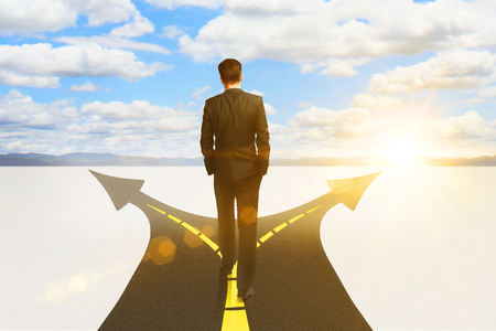 way of thinking: Success concept with thoughtful businessman standing on highway road leading to bright sky