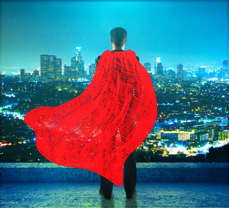 Businessman with red superhero cape standing on roof and looking into the distance on cityscape background