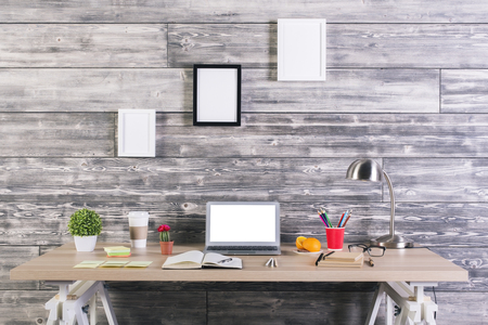Modern designer desktop with blank white laptop, picture frames above, plants, stationery and other items. Mock up