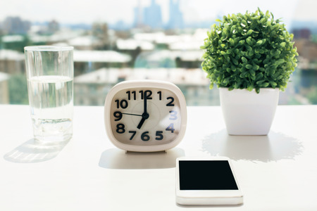 phone the clock: Closeup of white desktop with blank smart phone, clock, water glass and decorative plant on blurry city background with sunlight. Mock up