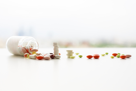 Closeup of white desktop with different pills falling out of prescription bottle on blurry city background