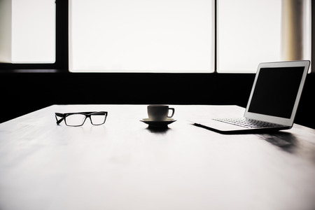 backlit keyboard: Backlit office desktop with blank laptop screen, coffee cup and glasses. Mock up