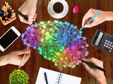 Creative thinking concept with hands drawing abstract colorful digital human brain on wooden office desk with blank cellphone, coffee cup, stationery items, calculator and decorative plant
