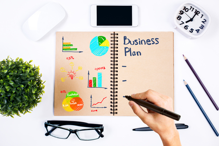 Hand writing business plan in spiral notepad placed on white office desktop with various items