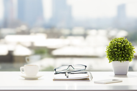 windowsill: Closeup of white desktop with coffee cup, glasses, notepad, smartphone and plant on blurry city background