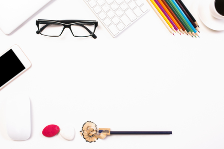 filings: Top view of white desktop with glasses, smartphone, colorful pencils, coffee cup and pencil filings. Mock up