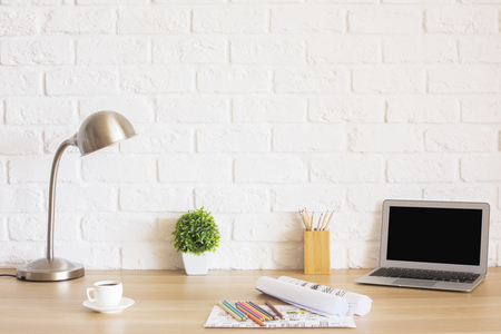 blank screen: Creative designer desktop with blank laptop screen, plant, coffee cup, sketches, colorful pencils, lamp and other items on white brick wall background. Mock up