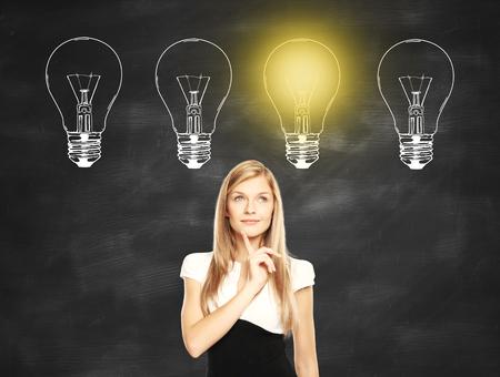 businesswoman standing: Idea concept with thoughtful businesswoman standing against chalkboard with illuminated drawn light bulbs Stock Photo