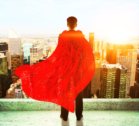 invincible: Businessman with red superhero cape standing on roof and looking into the distance on cityscape background
