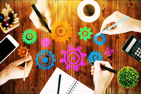 Team work concept with hands drawing abstract colorful cogwheels on wooden office desk with blank smartphone, coffee cup, stationery items, calculator and decorative plant