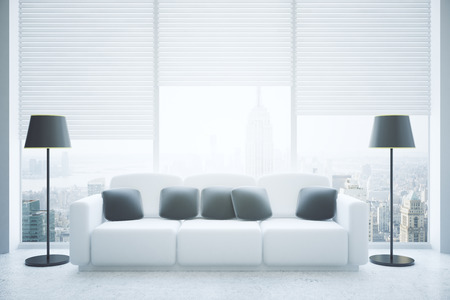 daytime: Front view of modern living room interior with black pillows on white couch, floor lamps, concrete floor and panoramic window with blinds and city view. 3D Rendering
