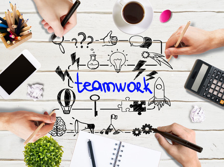 businesspeople: Teamwork concept with businessmen hands drawing sketch on light wooden office desk with blank smartphone, coffee cup, stationery and other items Stock Photo