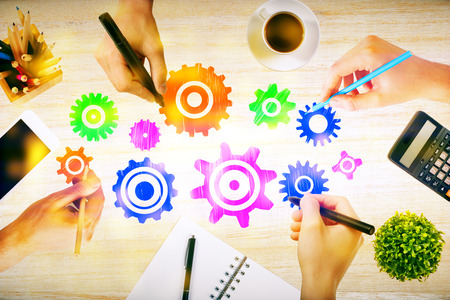 working desk: Team work concept with hands drawing abstract colorful cogwheels on wooden office desktop with blank smartphone, coffee cup, stationery items, calculator and decorative plant