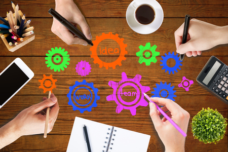 wooden work: Team work concept with hands drawing abstract colorful cogwheels on wooden office table with blank smartphone, coffee cup, stationery items, calculator and decorative plant