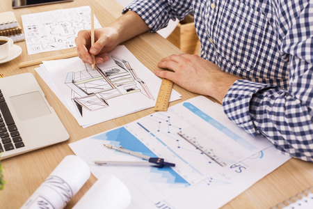 Side view of architect using ruler and pencil to draw blueprint on wooden office desktop with stationery items, business report, coffee cup and laptop keyboard