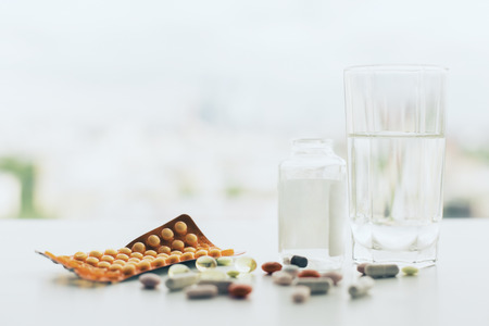 Closeup of white tabletop with different pills, glass of water, medicine bottle and package