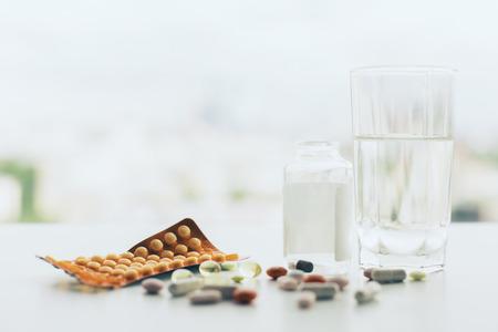 Nahaufnahme der weißen Tischplatte mit verschiedenen Pillen, Glas Wasser, Medizin-Flasche und Verpackung