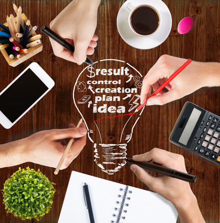 desk: Idea concept with businesspeoples hands drawing light bulb sketch on wooden office desktop with blank smartphone, coffee cup, other decorative and stationery items