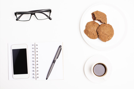 Top view of office desktop with blank cellular phone, notepad and pen, coffee cup, cookies on plate and glasses. Mock up
