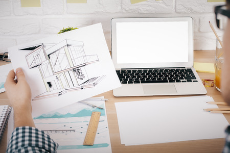 evaluating: Architect evaluating his construction project at office desk with blank white laptop, business report and stationery items. Mock up Stock Photo