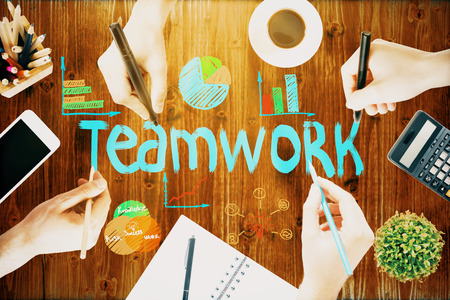 Teamwork concept with businessmen hands drawing sketch on wooden office table with blank smartphone, coffee cup, stationery and other items Stock Photo