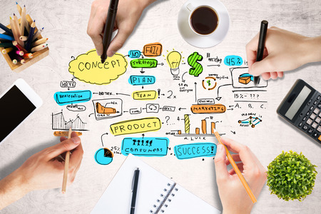 teachings: Success concept with businesspeople hands drawing sketch on light wooden table with blank smartphone, coffee cup, stationery and other items