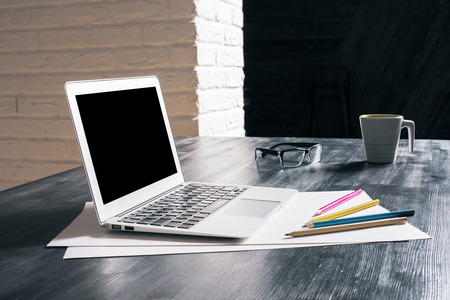 creative tools: Side view of creative designer desktop with blank laptop, coffee cup, glasses and drawing tools on white brick wall background. Mock up Stock Photo