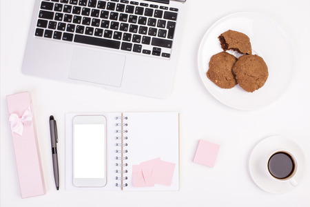 Top view of light girly office desktop with blank white smart phone, laptop keyboard, coffee cup, gift case, cookies on plate and other items. Mock up Stock Photo